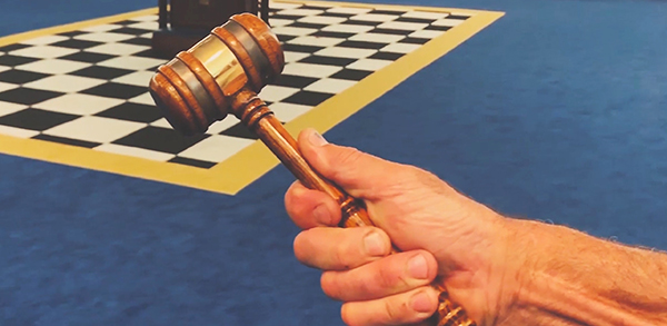 Hand holding a gavel in a lodge room